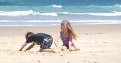 Bambini che giocano sulla spiaggia con la sabbia